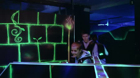 Group of young people with laser guns having fun on dark lasertag arena