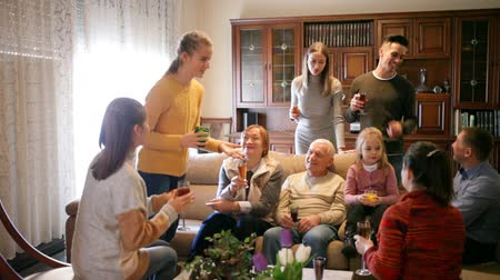 Happy large family gathered in parental home for family party, talking in cozy living room