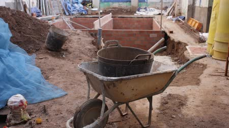 overhauls : View of building under reconstruction - tools and materials near pit with brick construction