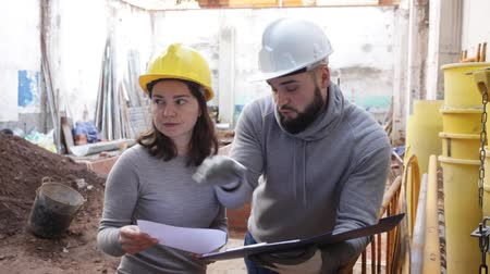 overhauls : Female architect and young contractor discussing construction plan at building site
