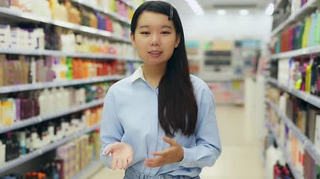 Portrait of friendly Asian female shop assistant near shelves with hair dye in cosmetics shop Stock mozgókép