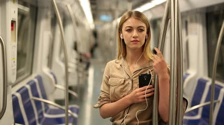 Young woman with a smartphone and headphones enters a subway car