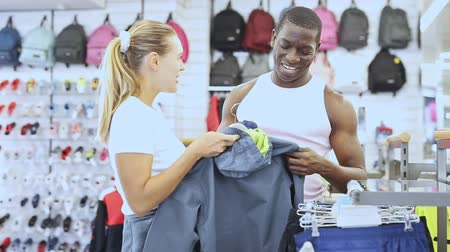 Portrait of cheerful couple of customers choosing sport clothes in sporting goods shop