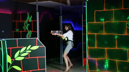 Emotional portrait of men and women co-workers having corporate entertainment in laser tag room