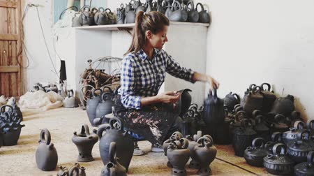 kamenina : Portrait of female potter holding and inspecting ceramics in pottery workshop