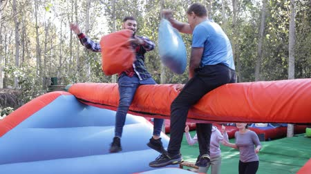 bounce : Guys having funny wrestling by pillows on inflatable beam in outdoor amusement playground