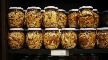 enlatamento : Glass jars with assorted preserved mushrooms on shelves in store