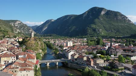 reddish : General aerial view of small French town of Tarascon-sur-Ariege in valley of Pyrenees on banks of Ariege river on summer day Stock Footage