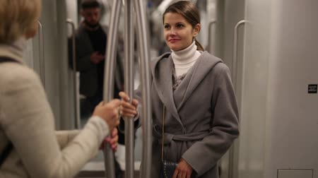cortes : Two women passengers talking in subway car on way to work