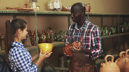 kamenina : African American shopman consulting woman visitor in pottery shop