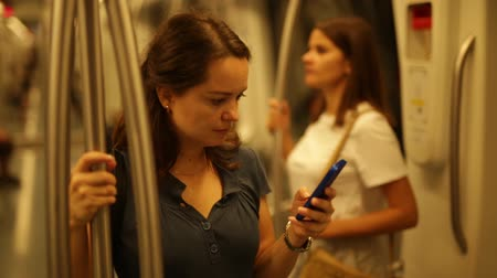 corrimão : Young focused woman standing in subway car holding on handrails, browsing in her smartphone
