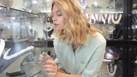 jasper : Cheerful girl trying on and choosing natural stone necklace in jewerely shop