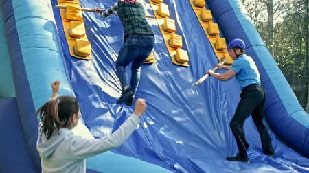 bounce : Male and female friends having fun in outdoor amusement park, climbing on inflatable castle Stock Footage
