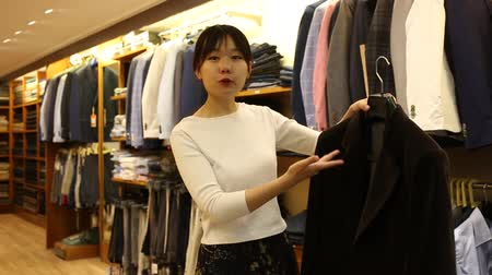 cortes : Polite young Chinese salesgirl offering stylish suit coats in men clothing store Vídeos