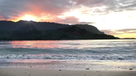 havaiano : On the sandy beach in Kauai Hawaii with a colorful sun setting behind the mountains Vídeos