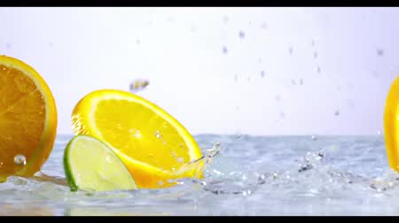slow motion of falling citruses into water Stock Footage