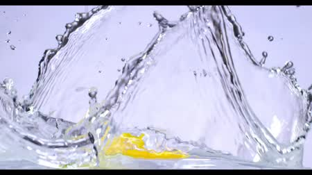 gotas de água : slow motion of falling lemon into water