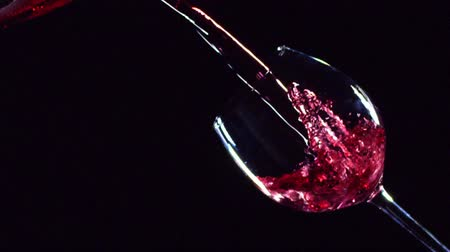 close up shot : Slow motion of pouring red wine from bottle into goblet