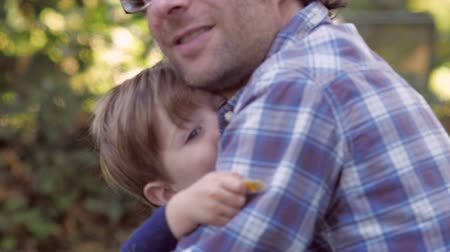gün : Little blond boy having fun and hugging his 30 something father outside in green yard with soft focus. Stok Video