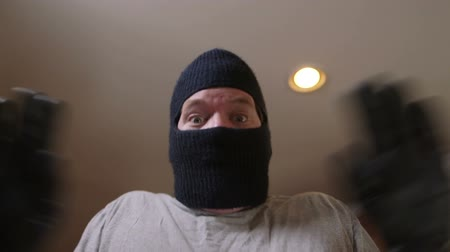 maszk : A man in ski mask - a burglar or thief breaking into a house is surprised as he begins falling backwards to the ground. Stock mozgókép