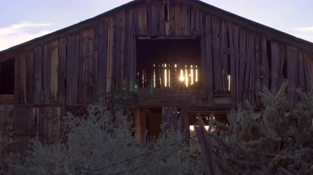 istálló : Old wooden abandoned brown barn with sun gleaming and streaming through open slats and beams in the dilapidated wood with sagebrush and plants in foreground with slow dolly move. Stock mozgókép