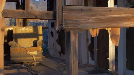 abandoned house : Abandoned old dilapidated house with broken window and old ruined chair furniture with open wall, pealing paint and wood moving in the wind, abandoned belongings, and sunlight streaming through broken wall and wood. Stock Footage