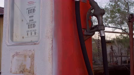 országúti : An old vintage red gas pump with an analog counter shows wear from time and age. Peeling paint and a cracked glass case is revealed with this dolly shot.