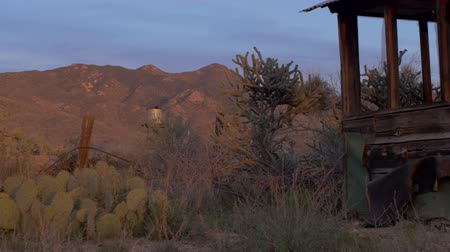 farpado : An old water tank, cacti, and abandoned house are seen during sunrise  sunset in the desert with a dolly shot.