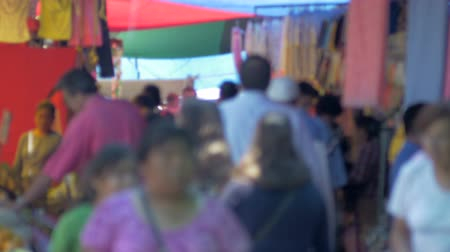 jídla : A crowded outdoor market in a latino country busy with shoppers walking by the camera out of focus.