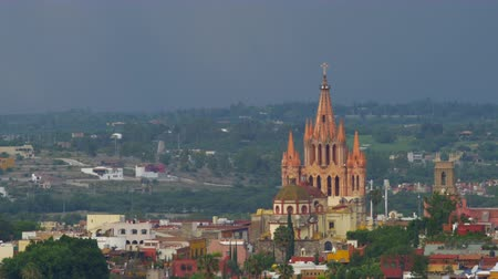 expat : Egrets fly past the iconic church in San Miguel de Allende, Mexico, otherwise known as el Jardin or the Parroquia during sunset with a storm in the background. Stock Footage