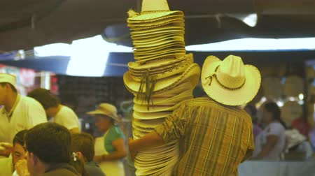 meksyk : Man walking through a busy outdoor market in Mexico carrying a large stack of cowboy hats. Wideo