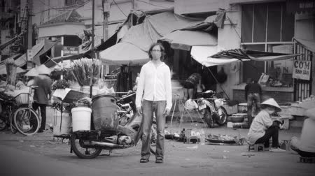 cant : Time lapse of a solitary man wearing a breathing mask to filter out pollution and toxic air stands still as the world around him flies by at a busy market where people are over consuming in black and white.