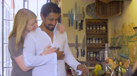 moderno : A young mixed racial couple in their 20s hug and kiss in the morning while the attractive latino man with facial hair cooks breakfast in a modern equipped kitchen wide dolly shot.