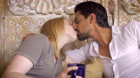 mroczne : An attractive young mixed race couple in their 20s show affection and intimacy together in a dolly shot where the latino man and white woman kiss, touch, and pay attention to one another.