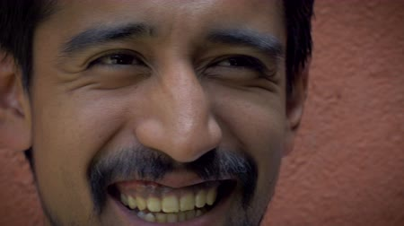 meksika : An extreme closeup portrait shot of a young handsome 20 something latino man with facial hair smiling at camera while standing up against an orange wall.