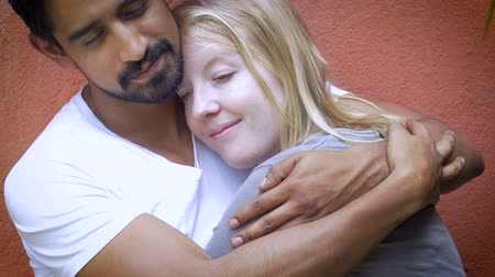 miłość : A very attractive mixed racial couple in love embrace, smile, and kiss against an orange wall showing affection and love for one another. Wideo
