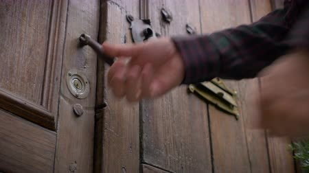 fogadtatás : A man opens an antique colonial brown wooden door with old brass lock and henge and walks through to his luxurious home.