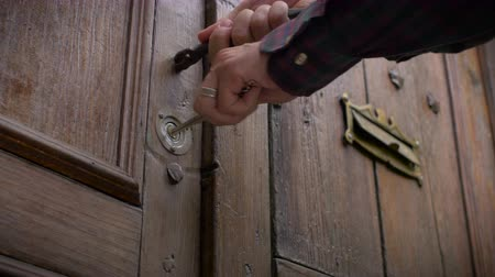 protects : Dolly shot of a man opening the front door of his house and turning to lock his antique brown wooden colonial door with brass lock and henge and then walking away from his house in a basic security measure.