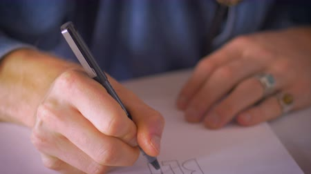 workshop : A young self employed artist concentrates on his job of creating an art by hand with a pen on white paper in a notebook as camera pans from his face to a close up of his hands. Stock Footage