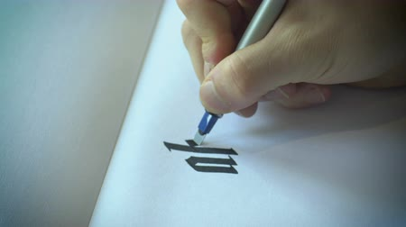 yazarak : A close up shot of writing the alphabet in calligraphy on white paper.