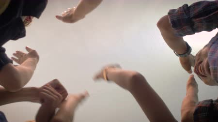 munkahelyek : Low angle shot from below of a group of 5 young millennials place their hands together in the center of a circle and then cheer in a celebration of a successful event and shake hands and fist bump. Stock mozgókép