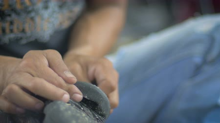 wasteful : Close up of a man working with his hands as he prepares a rubber shoe sole for glue to properly adhere to the base using sand paper. This roughens the surface so the adhesive will secure to itself. Stock Footage