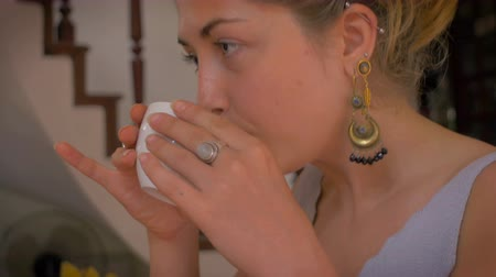 koflík na čaj : Hand held shot of a young 20 something attractive, thin woman wearing dangle earrings takes a sip of hot coffee from a white tea cup and smiles feeling refreshed and satisfied.