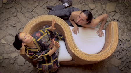 moderní : Overhead shot of two traditional butoh dancers - one shirtless - one is blowing kisses to his Japanese partner while she freaks out in fast sharp movements.