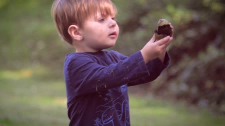 доверие : An innocent young child holding up something and asking what it is in slow motion. He is curious about his environment and wants to learn about the beauty of nature.