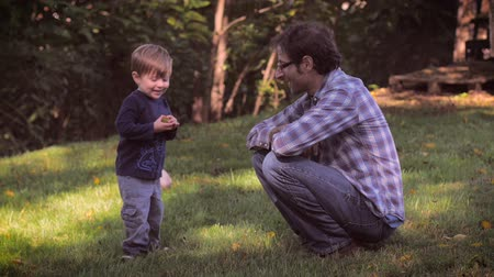 yards : A father wearing glasses and a 2 year old child spending time together outside in nature in slow motion. The child is running with excitement with his new object as the camera follows him.