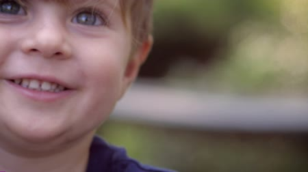 yards : Close up and handheld portrait of a young blond cute healthy boy smiling and playing outside in a park or the back yard of a residential home anywhere with shallow depth of field.