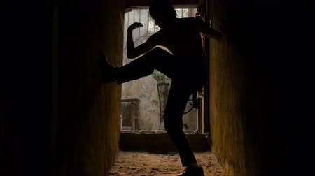 ruhanilik : The silhouette of a man climbing up a stone wall in a dark ally in a dance performance. Stok Video