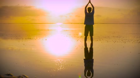 inspiração : Thankful man stands in still water of the ocean with hands reaching out towards the sun in a worship pose then moving into a lotus position looking for inspiration at sunrise or sunset with his reflection in the water below him.