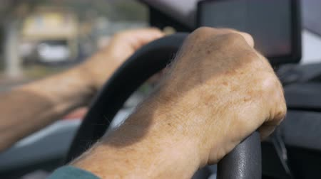 błąd : Hand held close up of hands on a steering wheel, driving, while operating a GPS in a car during the day